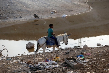 Boy rides a donkey past a wastewater pond in the Palestinian Bedouin village of Khan al-Ahmar that Israel plans to demolish, in the occupied West Bank