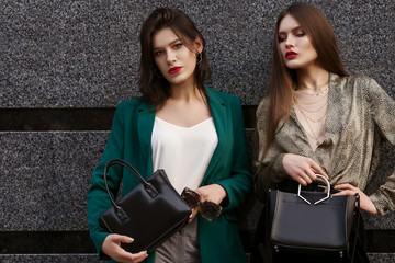 Outdoor fashion portrait of two young beautiful fashionable women wearing, stylish clothes, holding black leather bags, posing in street, on gray background. Copy, empty space for text