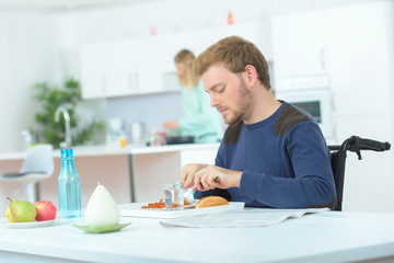 man disabled on wheelchair eating lunch