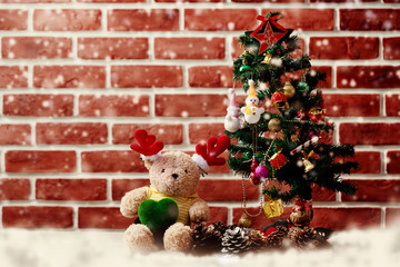 Accessories Christmas and Happy New Year Both teddy bears. Christmas tree Adorned with snow dolls gift boxes Pine cones placed on the floor In room with red wall. Decoration in festivals of happiness.