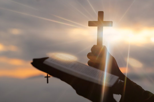 Silhouette of human hand holding the cross with bible, the background is the sunrise., Concept for Christian, Christianity, Catholic religion, divine, heavenly, celestial or god.