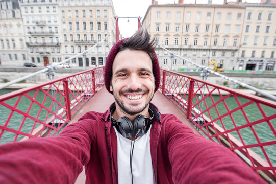 Urban selfie of an handome man smiling at the camera on vacation