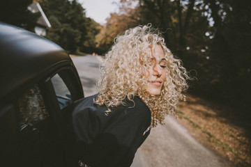 Woman with eyes closed leaning out of car window