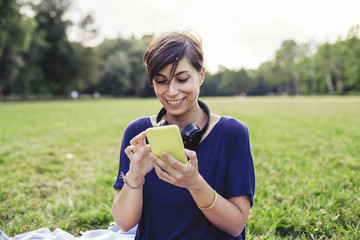 Young adult woman using a mobile phone at the public park