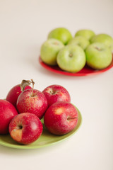 Red and green apples on a plate on a white background.