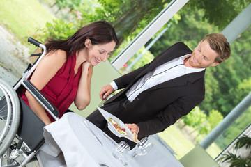 handsome waiter bringing order to happy disabled mature female