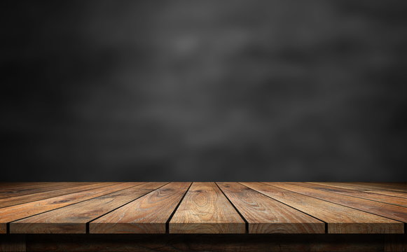 Wooden table with dark blurred background.