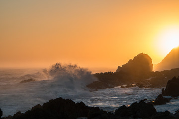 Ocean sunset with wave breaking onto silhouette rocks.