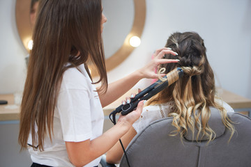 Process of making trendy hairstyle in beauty salon