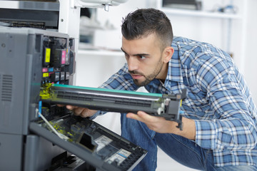 repairman fixing cartridge in photocopy machine at office
