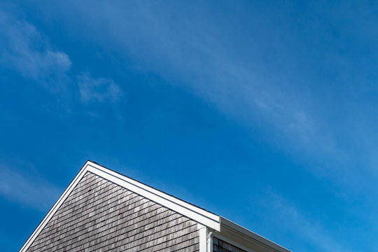 A blue sky with wispy clouds stands about a peaked roof with a wooden shake shingle siding. This is a horizontal image.