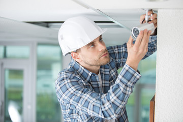 technician installing camera on wall with screwdriver