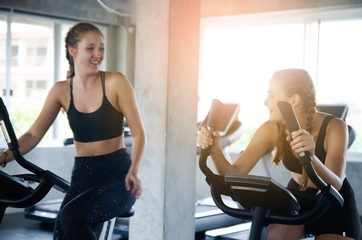 Young people talking and smiling while working out on bike at gym. Friends in a conversation while cycling on stationary bike in fitness centre. Group of happy people working out at spinning class.