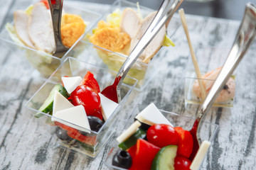 Fresh salad with cheese and tomato in a glass. Catering.
