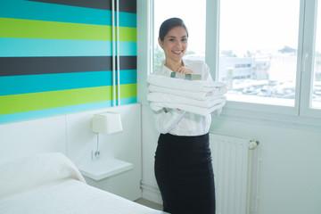 happy housekeeper in hotel room