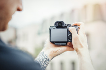 Close up of man hands holding camera and making photos of modern building.