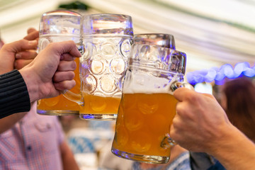 A group of young people Friends toasting with glasses of beer at the Oktoberfest germany Soft focus. Shallow DOF