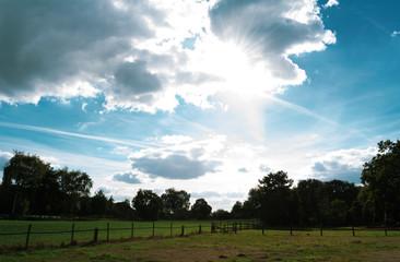 schöner abendlicher, hell leuchtender, Wolkenhimmel über Felder und Wiesen. Standort: Deutschland, Nordrhein - Westfalen, Borken
