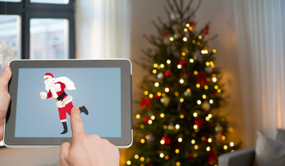 holidays and technology concept - close up of hands holding tablet pc with santa image on screen over christmas thee lights background