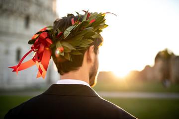 Giovane ragazzo laureato con corona d'alloro in testa e vestito elegante visto di spalle. Corona Trionfale simbolo di sapienza e gloria,.