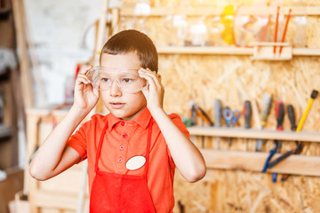 boy in the workshop independently learns to work with wood in the carpentry workshop. The concept of a useful hobby in childhood and learning to work manually with hands