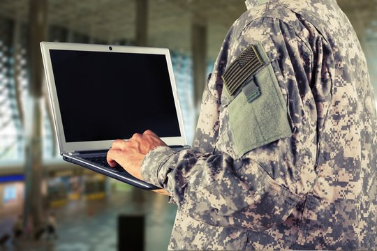 Young military soldier man portrait with laptop