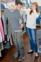 Couple in shop, man holding clothes against himself