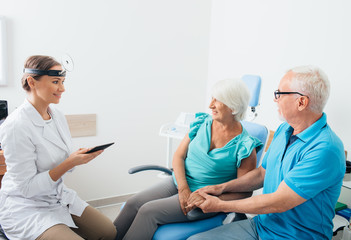 Mature couple, senior patients in ENT clinic talking with doctor