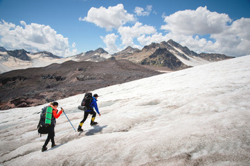 Two tourists, a man and a woman with backpacks and crampons on their feet walk along the glacier against the background of the mountains of the sky and clouds. Back view