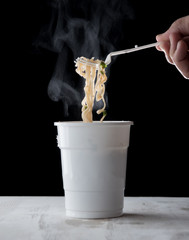 Hand holding plastic fork of hot instant noodles with steam and smoke in white cup