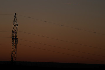 An airplane flies over an electricity pylon at sunset in Aranda del Duero