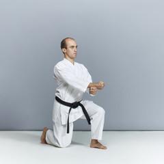 Athlete doing formal karate exercises in white karategi