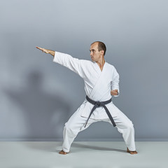 Sportsman in white karategi and with black belt is doing formal karate exercises on gray background