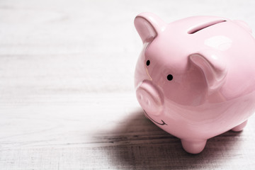 A Pink Smiling Piggybank On A Table