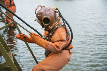Diver immerses in a vintage deep sea diving suit