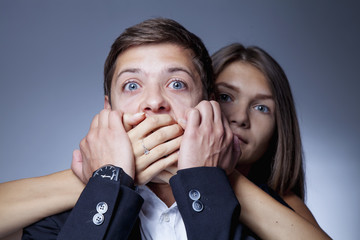 Gender terror and aggression: woman covers man's mouth. (Fear, gender inequality, violence, domination concept)
