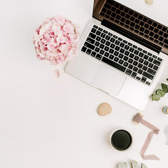 Modern home office desk workspace with laptop, pink hydrangea flowers bouquet, coffee cup, eucalyptus branch, monstera leaf plate and accessories on white background. Flat lay, top view.