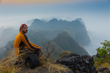 man sitting on stone top of high mountain