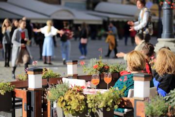 Obraz Kobiety piją pomarańczowe napoje w restauracji, ludzie tańczą na rynku miasta. - fototapety do salonu