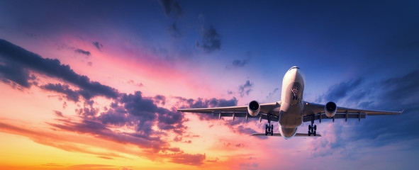 Tuinposter Vliegtuig Landing airplane against colorful sky at sunset. Landscape with aircraft is flying in the blue sky with orange and pink clouds. Travel background with passenger plane. Commercial airplane. Private jet