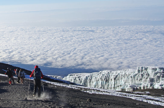 People walk at the top of the kilimanjaro in Tanzania above the clouds