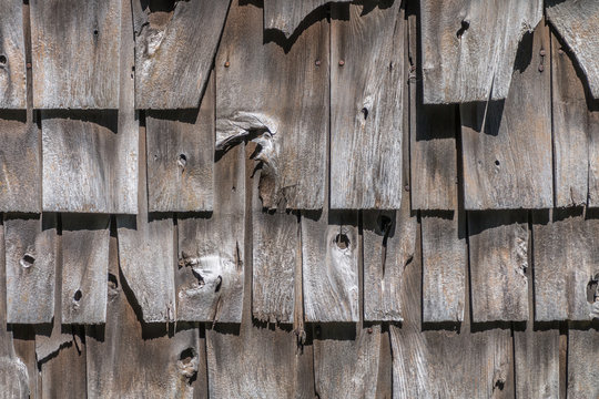 Wooden shake shingles are on the side of a building. The wood is old and graying. Some shingles are broken.
