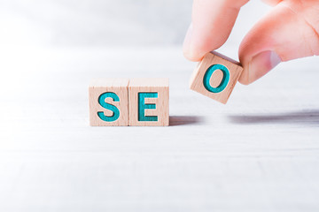 The Word SEO Formed By Wooden Blocks And Arranged By Male Fingers On A White Table