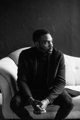 Young black man in coat on dark background sitting on a blue sofa crossed his fingers. black and white portrait