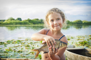 In the summer of bright sunny day a little girl on the river caught a large bream.