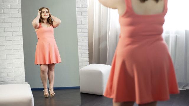Joyful fat female in dress admiring her mirror reflection, enjoying being plump