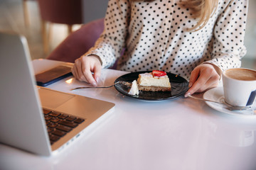 Girl eating cake in a cafe. Blonde in polka-dot shirt with laptop