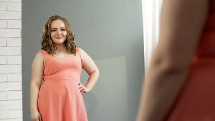 Plump lady looking in mirror with charming smile, self-confidence, body positive