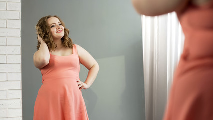 Charming plump lady looking in mirror and admiring herself, body positive