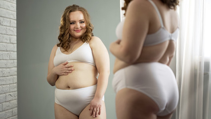 Self-confident plump girl looking in mirror, totally admiring her appearance